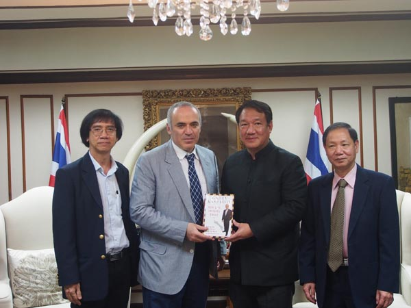 Kasparov presents his book to Mr Kittiratt; with Mr Panupand and Ignatius flanking them