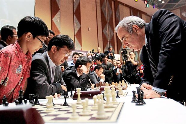Thoughtful: Garry Kasparov (right) and TalentCorp Malaysia CEO Johan Mahmood Merican contemplate their game, as Johan's son Kieran (left) looks on. Also pondering their next move are (from third left, seated) Royal Selangor executive director Chen Tien Yue and Pelaburan Mara chairman Datuk Sohaimi Shahadan. – MOHD SAHAR MISNI/The Star