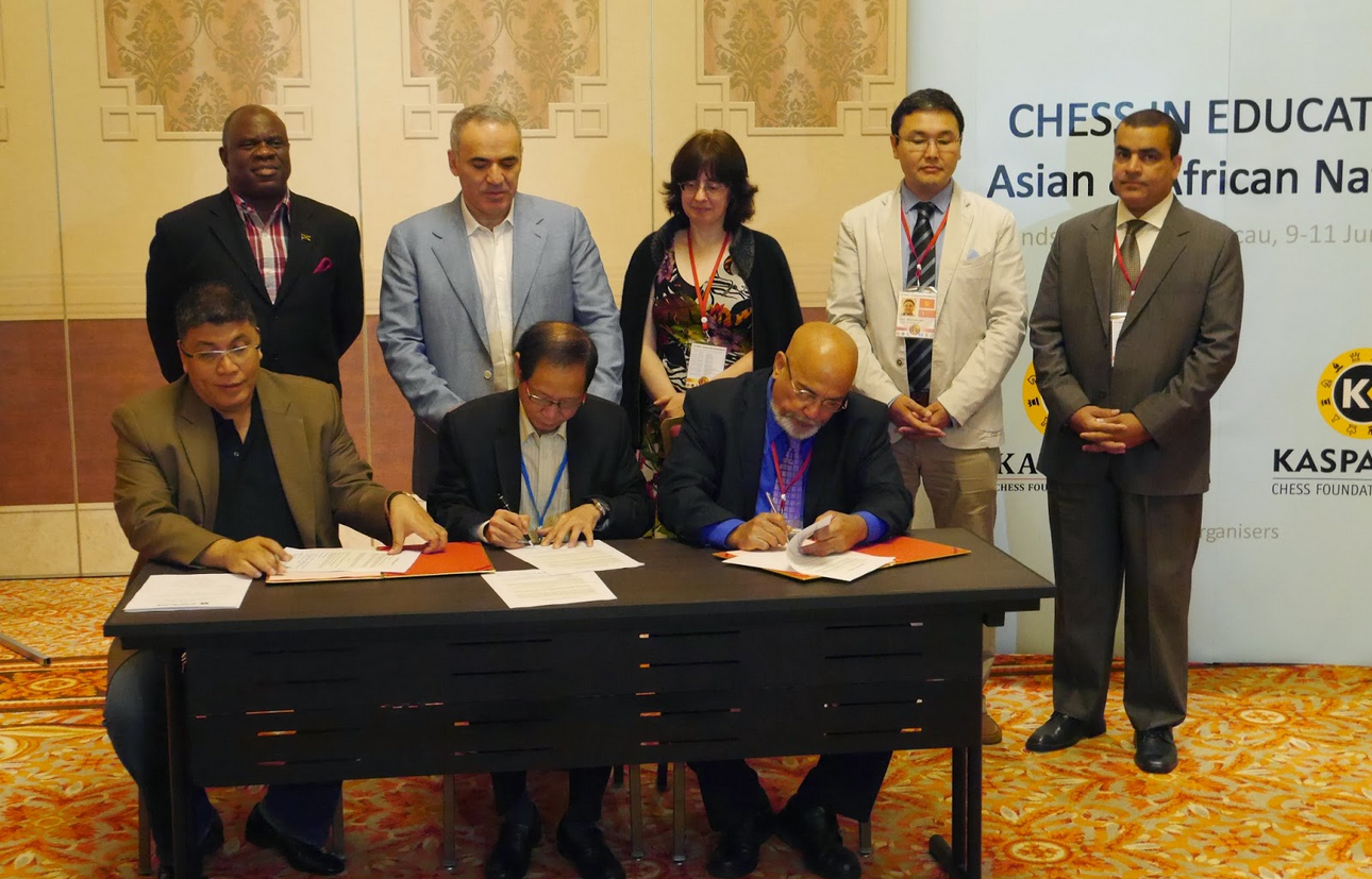 (Leon Ramos-Ryan signing the agreement with Prospero Pichay Jr and Ignatius Leong with members of Team Kasparov 2014 looking on)